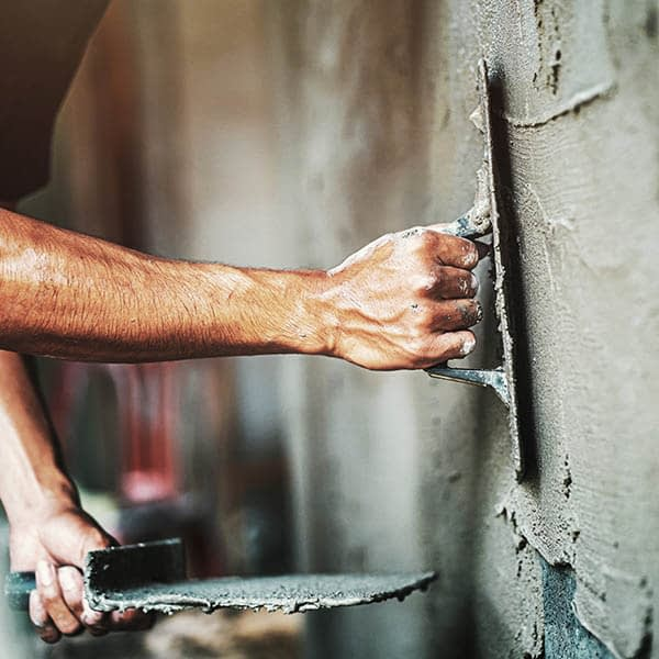 Worker plastering cement on wall - building materials