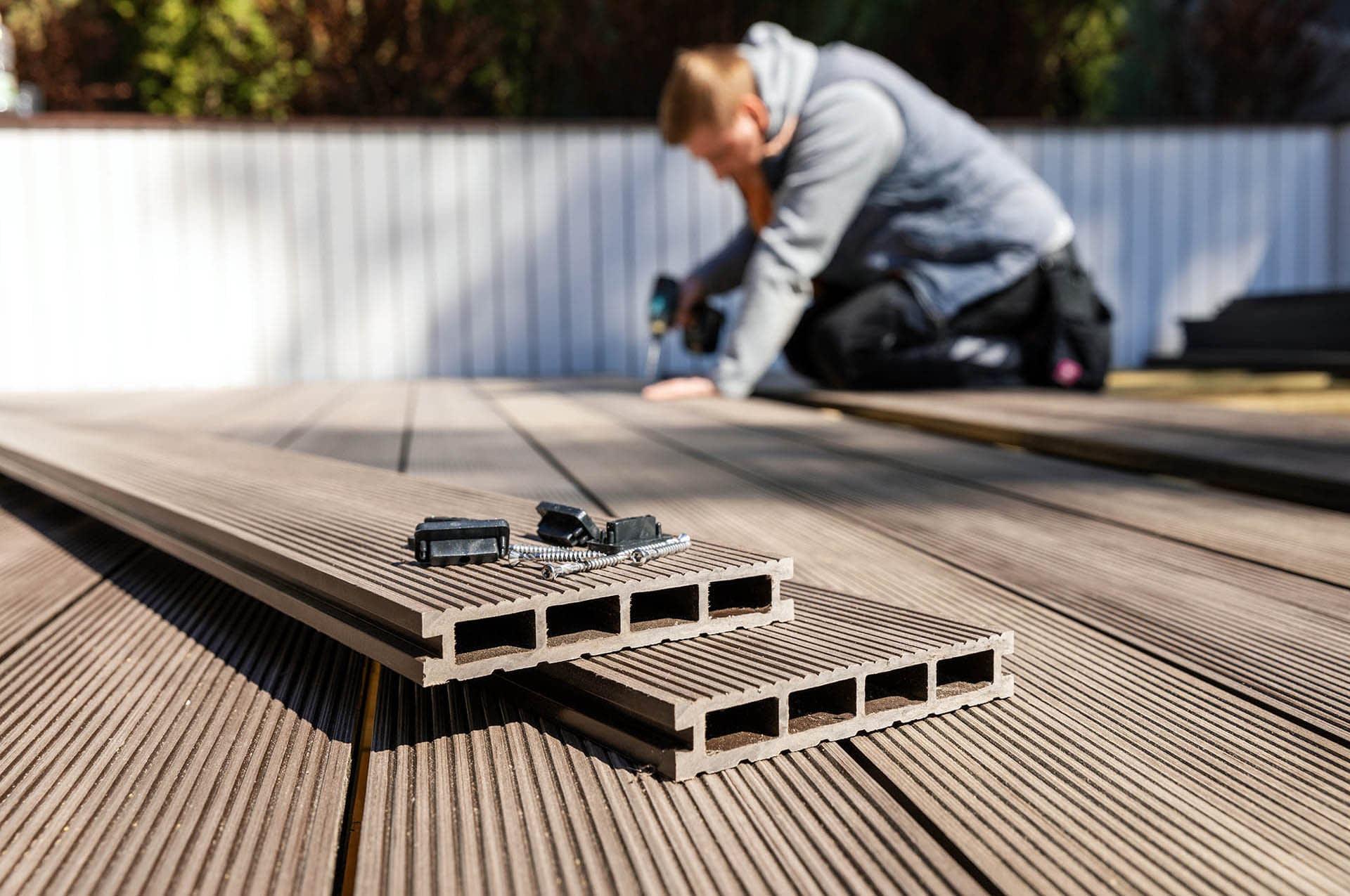 Worker installing wood plastic Cladco composite decking boards - composites alternatives
